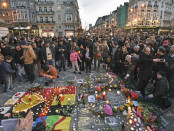 People bring flowers and candles to mourn at  the Place de la Bourse in the center of Brussels, Tuesday, March 22, 2016. Bombs exploded at the Brussels airport and one of the city's metro stations Tuesday, killing and wounding scores of people, as a European capital was again locked down amid heightened security threats. (AP Photo/Martin Meissner)